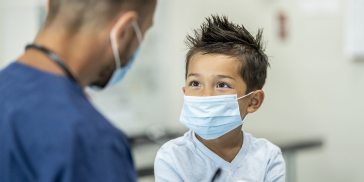 Paediatrician doctor examining a child while wearing a protective face mask in a clinic setting to protect from the transfer of germs during COVID-19.